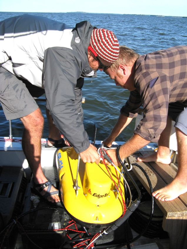 Devin Hougardy and Aaron DeRusha deploy the towfish used to take seismic profiles of the lake bottom.